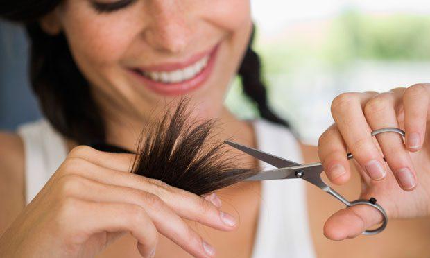 Mulher cortando as pontas do cabelo